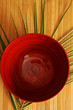 Red glazed bowl on palm frond and wooden table