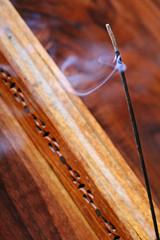 Burning stick of incense in carved holder