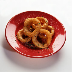 Seasoned onion rings served in the red dish