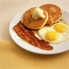 Pancakes with eggs and bacon served on the table