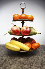 Various fruit are arranged on a metal three-tiered stand