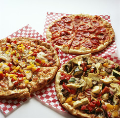 Three pizzas with delicious toppings placed on the table