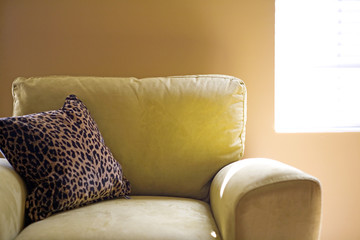 Yellow suede armchair with leopard print pillow