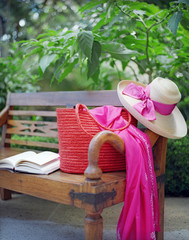 A hat and a scarf along with a hand bag and a book are kept on the bench
