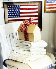 A small wooden house tied with a ribbon is kept on a pile of shirts