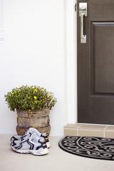 Running shoes placed beside a door and doormat