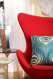A patterned throw pillow on a contemporary red wing chair
