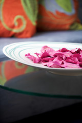 A shallow dish holds pink rose petals for a delicate centerpiece