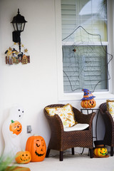 An array of different jack-o'-lantern decorations on a porch