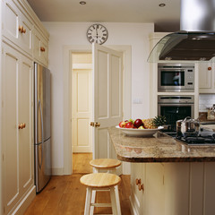 Two wooden stools are kept near the counter in an exquisite kitchen