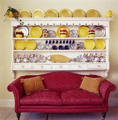 Red Couch Beneath Yellow Plates on Cupboard