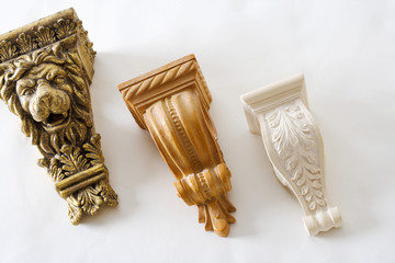 Decorative carved shelf supports made of plaster and painted wood