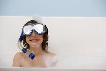 A little boy happily wears snorkeling gear in the bathtub