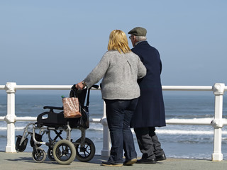 Anciano paseando acompañado