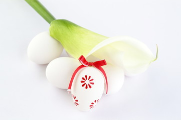 Easter eggs and calla lily on white background