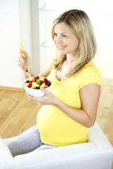 junge schwangere frau isst obstsalat