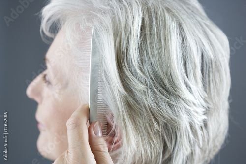 A senior woman combing her hair