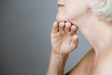 A senior woman touching the skin under her chin