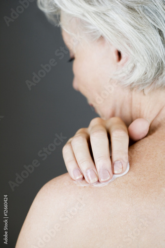 A senior woman applying moisturising cream to her shoulder