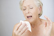 A senior woman sneezing