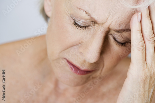 A senior woman with a headache, touching temples