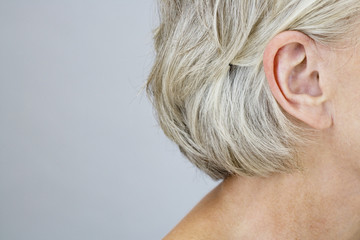 A senior woman showing her right ear and neck