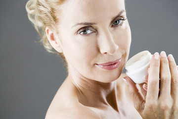 A middle-aged woman holding a pot of moisturising cream