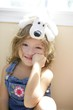 Happy toddler girl with toy dog over head