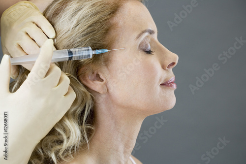 A middle-aged woman receiving a botox injection
