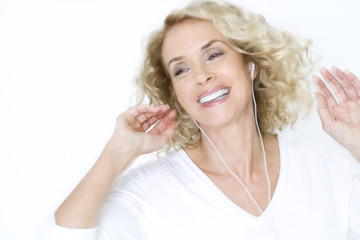 A middle-aged woman listening to mp3 music player, dancing