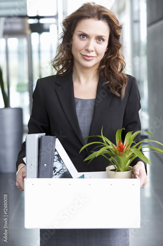 A redundant businesswoman taking her belongings home in a box