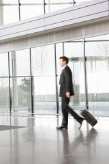 A businessman pulling suitcase along