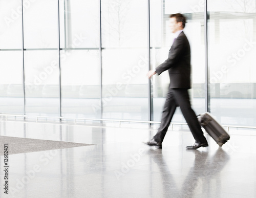 A businessman pulling suitcase along