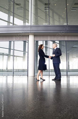 A businessman greeting a female client
