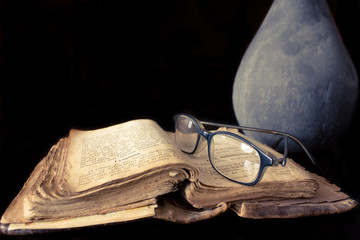 Ancient prayer book and glasses