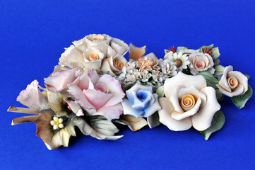 Bunch of ornamental ceramic flowers (like Capodimonte) on blue