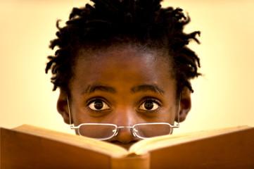 Junge schaut über ein Buch