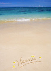 "The word ""Hawaii"" is written on a sandy beach"