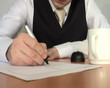 businessman writing on piece paper