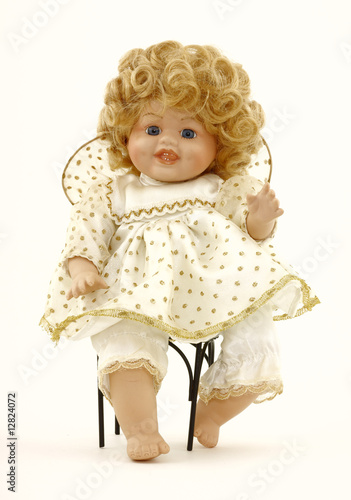 A baby doll in her own wrought iron chair.