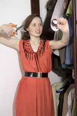 Young furious woman want to cut shirt-sleeve of husband`s shirt.