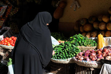 Veiled Muslim Egyptian Woman buying the vegetable