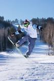 Fototapeta Snowboarder launching off a jump