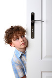 Boy peeking behind door