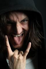 Young man with characteristic heavy metal tongue gesture
