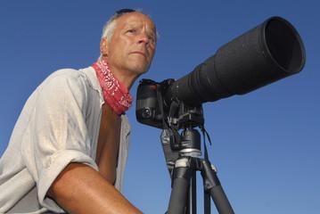 Handsome mature man adventurer posing with a big camera outdoors