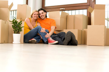 Couple on floor next to moving boxes