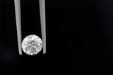 one carat diamond held by tweezers on black background poster