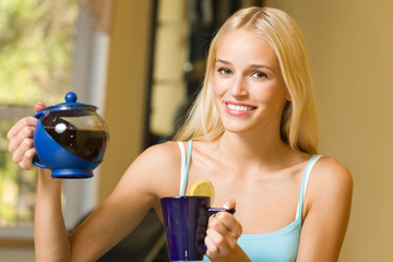 Portrait of young beautiful happy woman with teapot, indoors