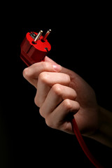 Hand holding power plug isolated on black background
